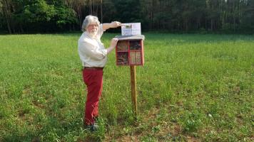 Linkshänder Manfred Neugebauer nagelt eine Erinnerungstafel an das Insektenhotel